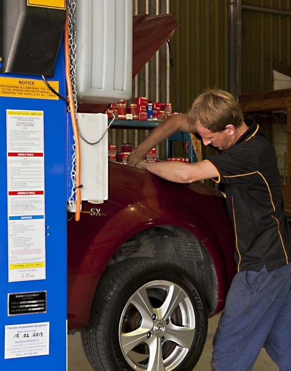 An employee shown fixing the engine in the bonet of a car in Albany Creek Auto Centre's garage