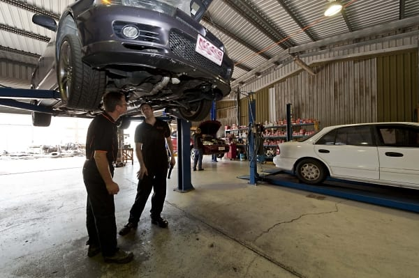Two employees shown fixing the muffler of a car in Albany Creek Auto Centre's garage